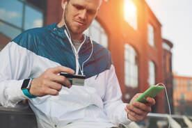 A picture of a man wearing running clothes looking confused at his credit card in one hand and phone with earphones plugged in in the other hand.