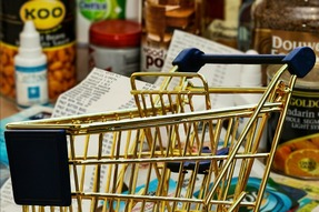 A picture of a grocery cart, a long grocery store receipt, and items you'd purchase from the grocery store.