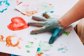 A child's hand covered in paint, finger-painting a heart.